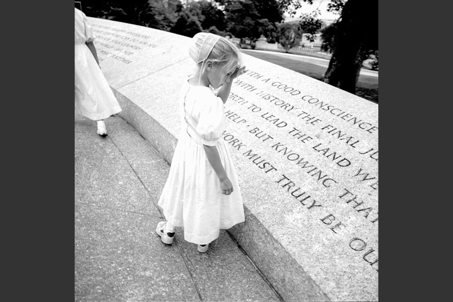 A girl reading an inscription in stone.