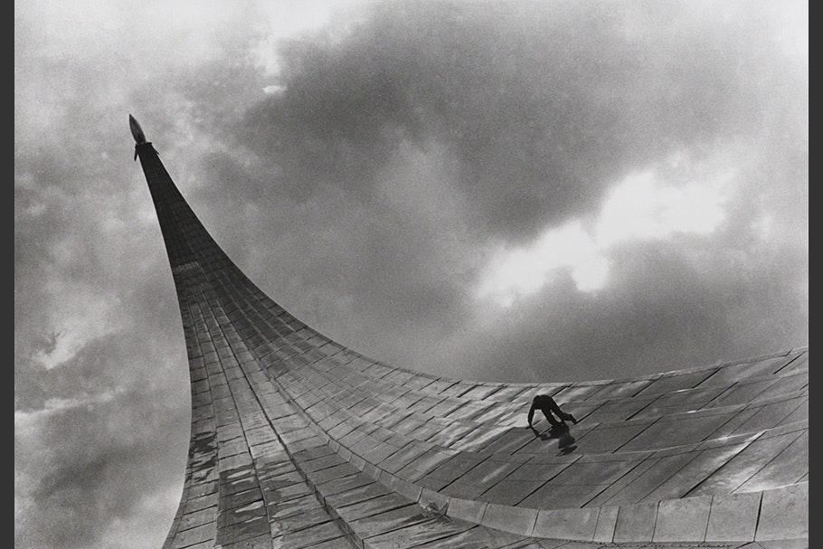 A boy climbs up a metal monument.