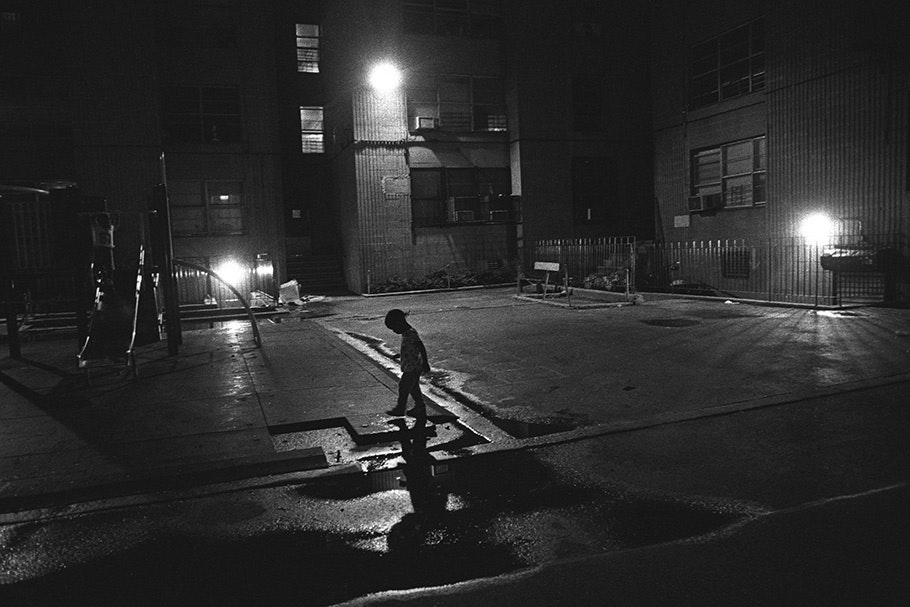 A child walking by a playground at night.