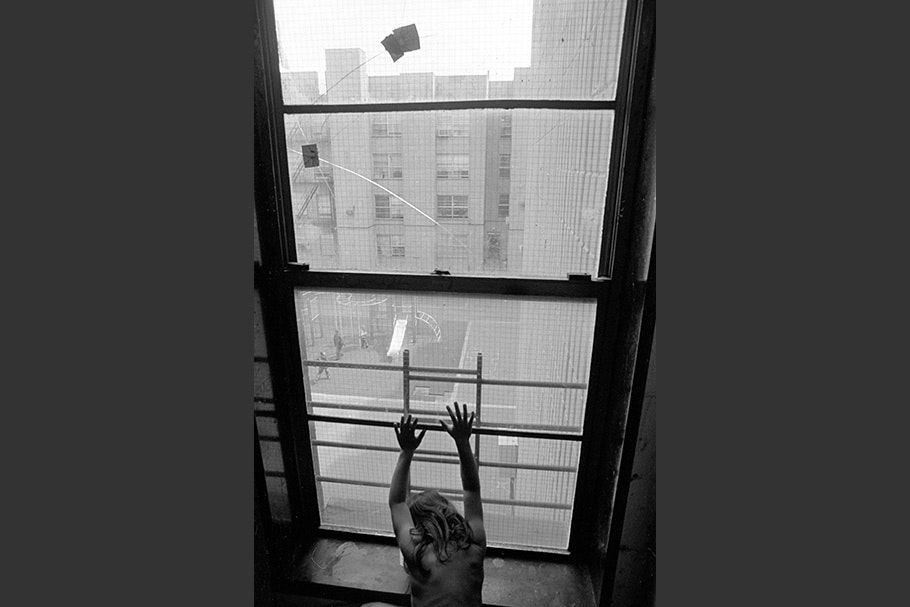 A girl with her hands against a window.