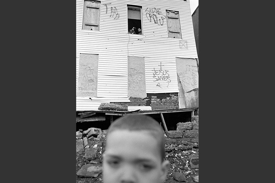 A boy in front of a rundown house.