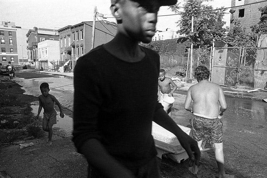 A man walking by a group of kids.