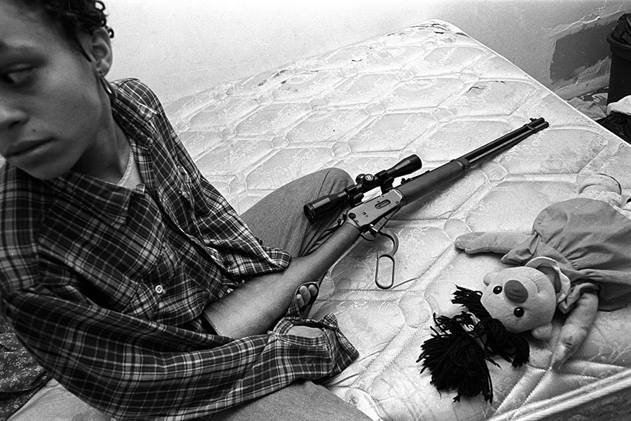 A woman with a gun and a doll on a mattress.