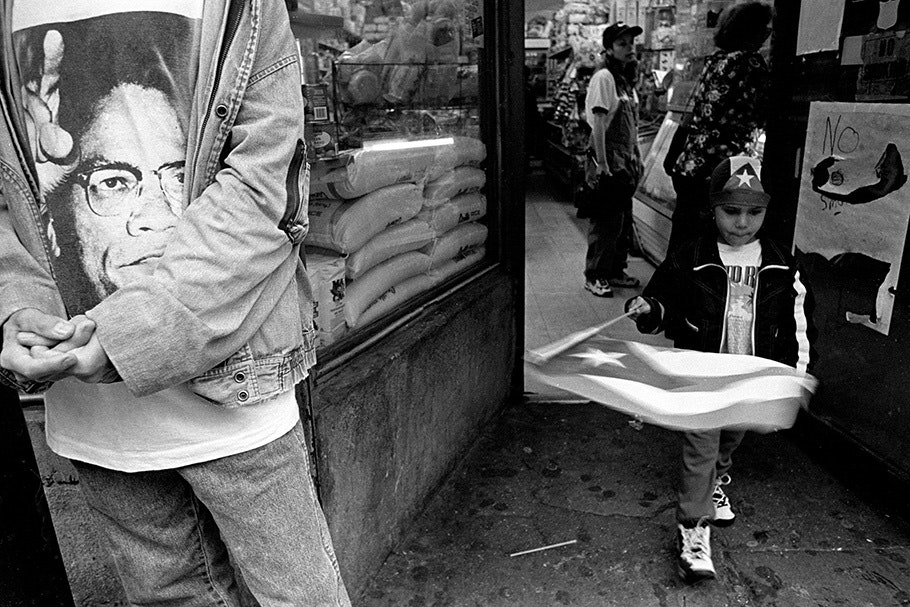 A child with a flag next to someone in a Malcolm X T-shirt.