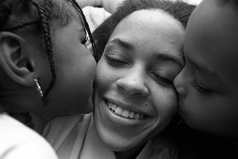 Two children kissing a woman's cheeks.