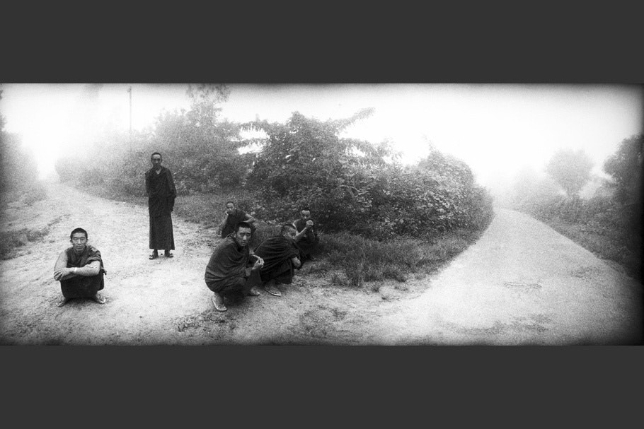 Panorama of six monks on a dirt path