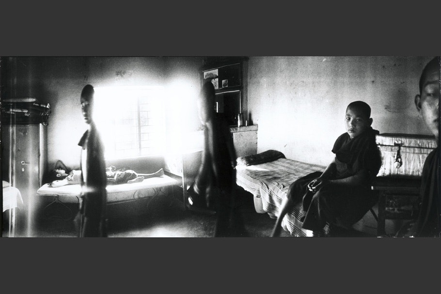 Panorama of young monks in a room with beds.