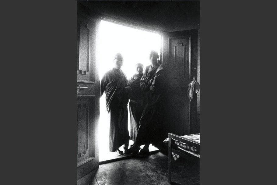 Three monks standing in a doorway