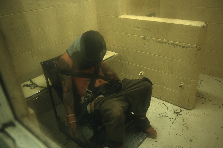 A man restrained to a chair with his head covered.