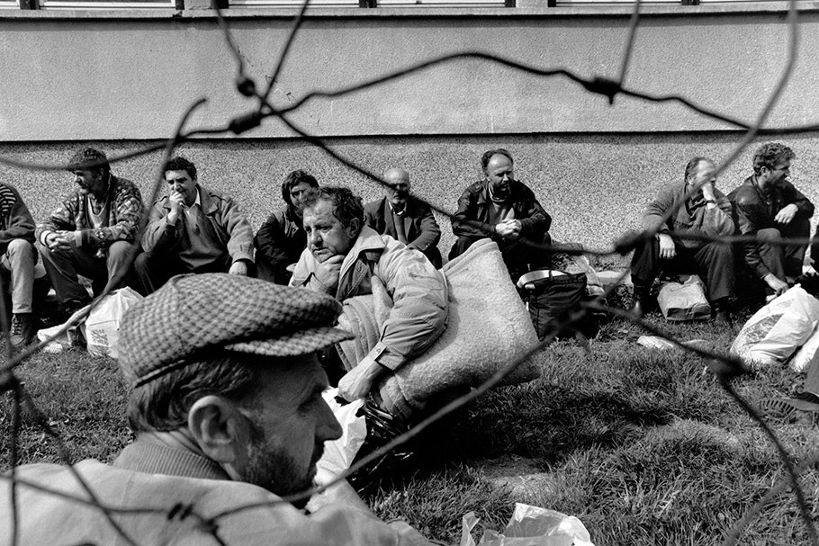 A group of men viewed through wire.