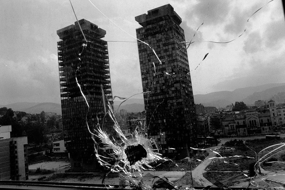 Tall buildings seen through a broken window.