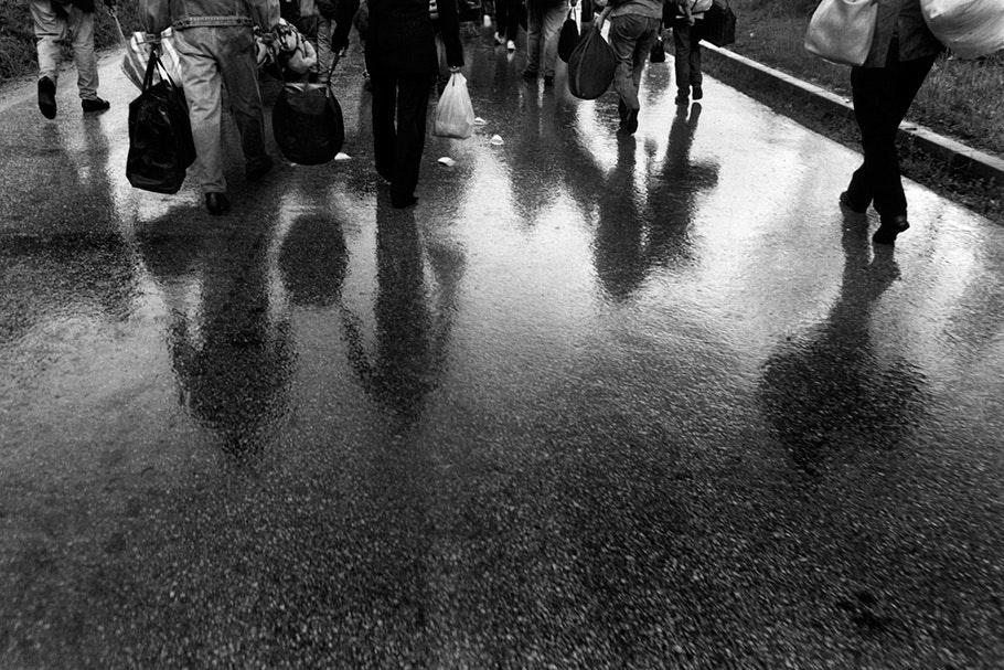People walking on a wet road.