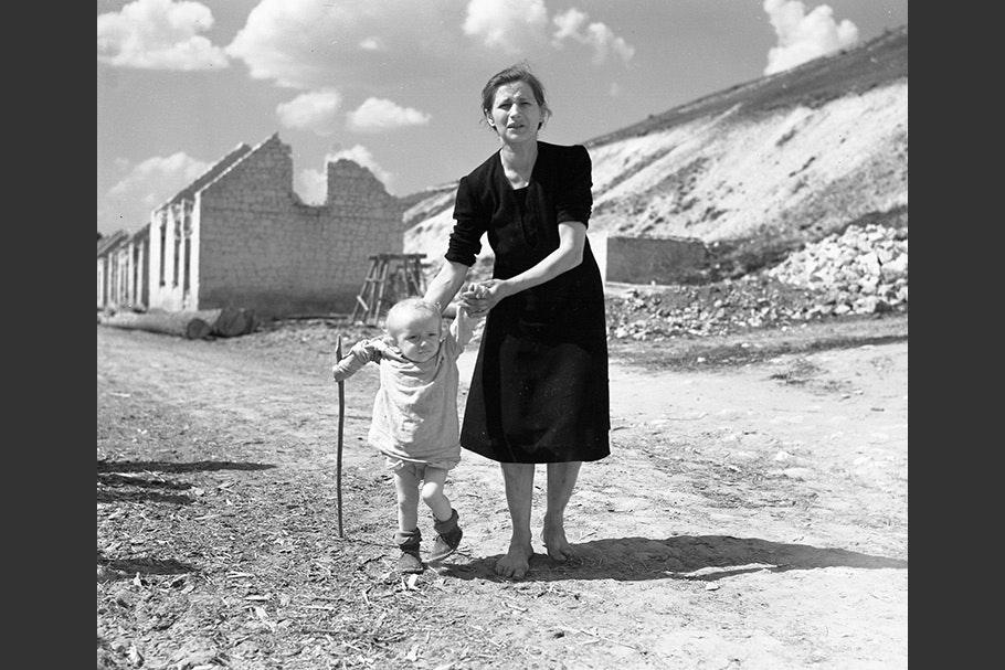 A mother and child walk down a ruined street.