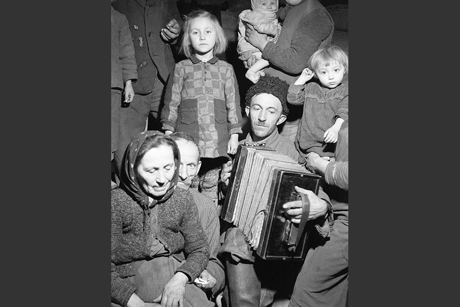 A group of people surrounding a man with an accordion.