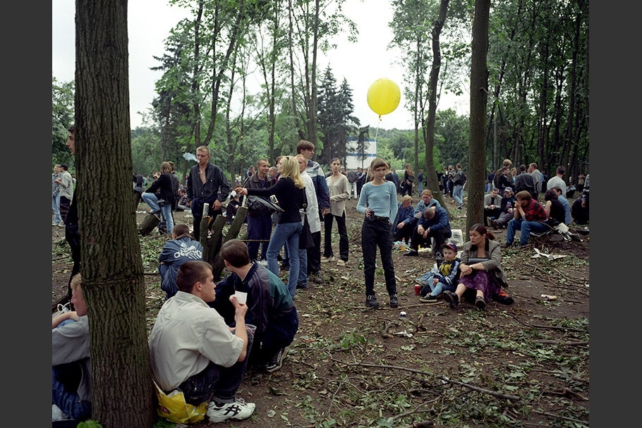 A crowd of people in a park. One girl holds a yellow balloon.