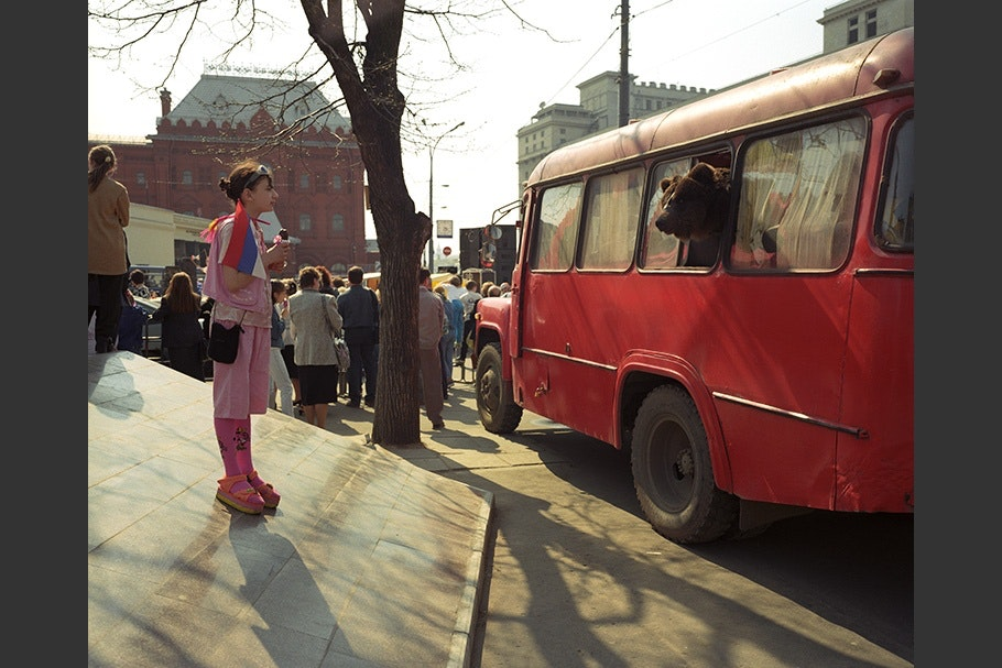 A girl looks at a bear in a bus.