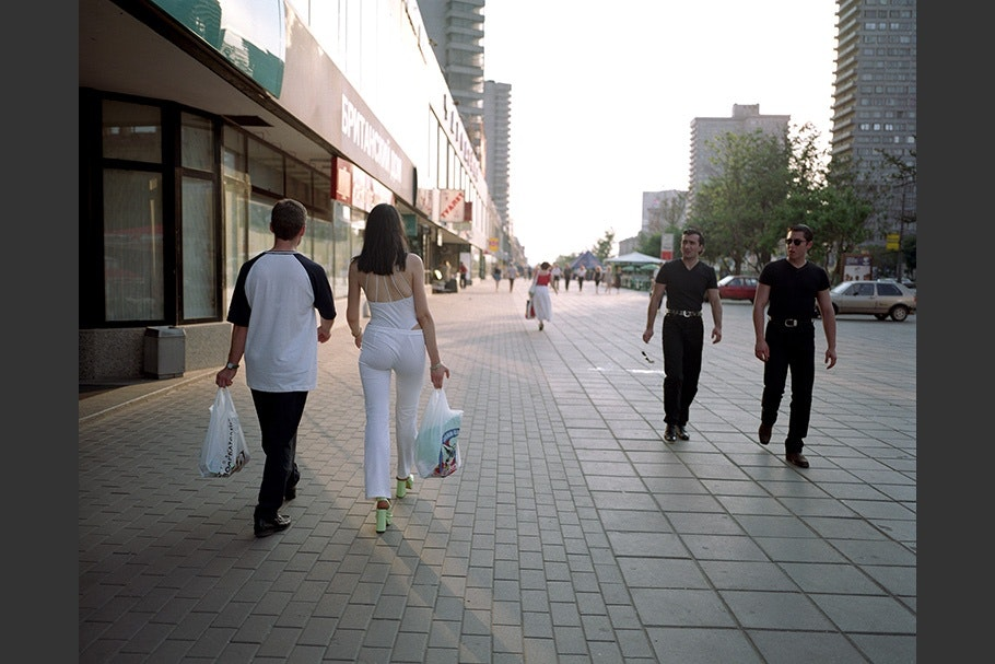 Pairs of people walking down a street.