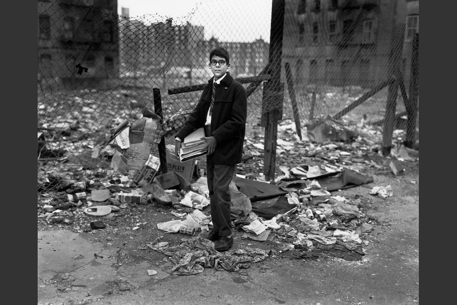 A boy carrying books past a vacant lot.