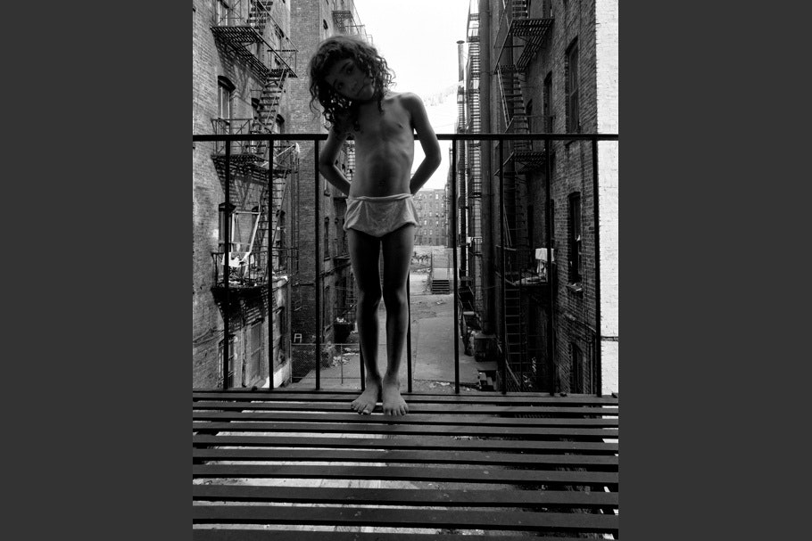 A child standing on a fire escape.