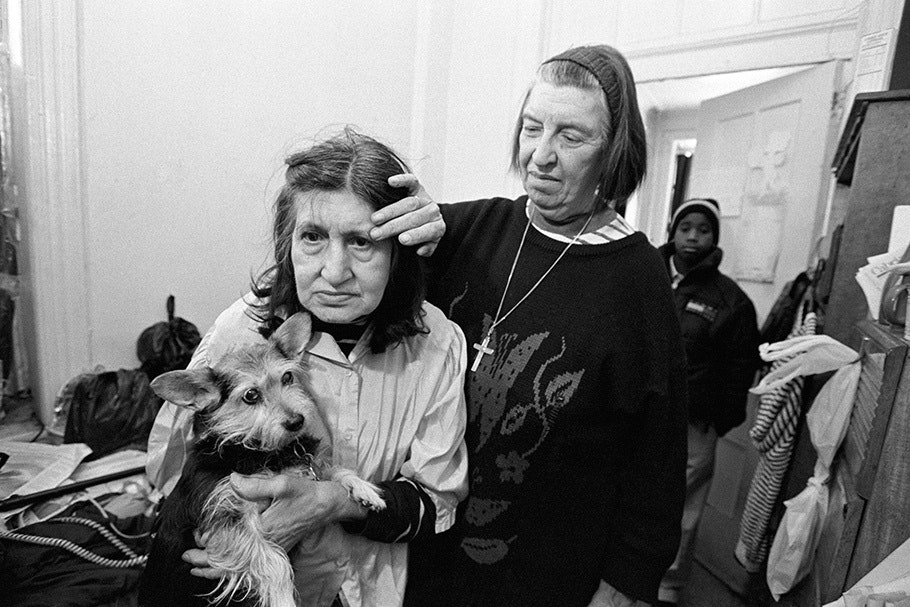 A nun comforting a woman with a dog.
