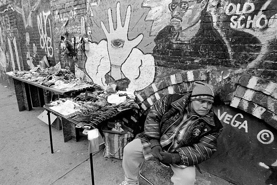 A man selling goods in front of a wall mural.