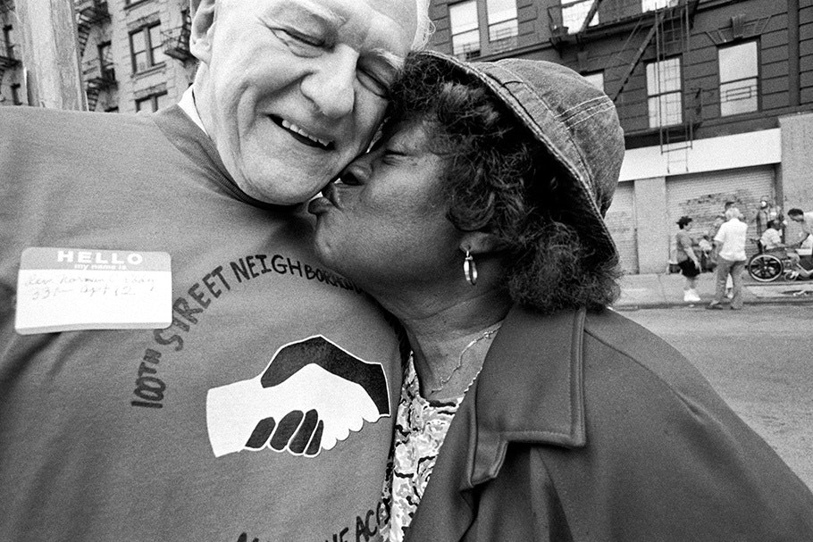 A woman kisses a man on the cheek.