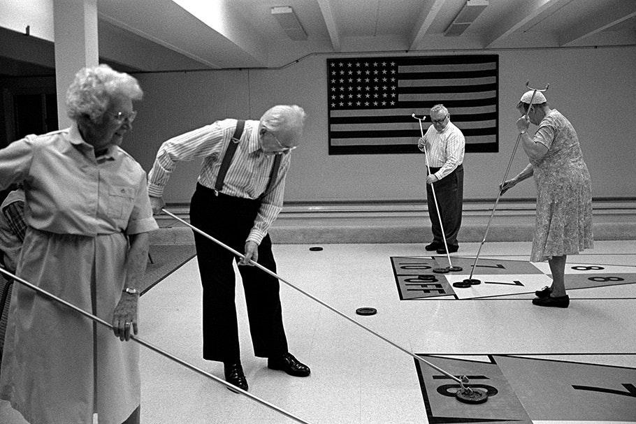 A group of senior citizens playing shuffleboard.