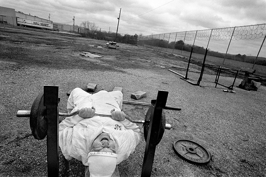 An inmate lifts weights in a prison yard.