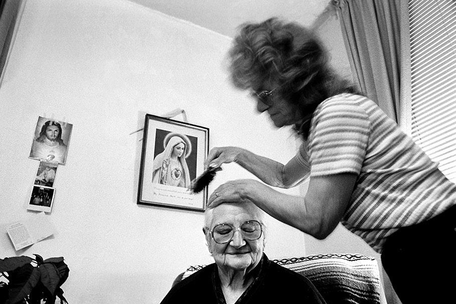 A caregiver brushes an elderly woman's hair.