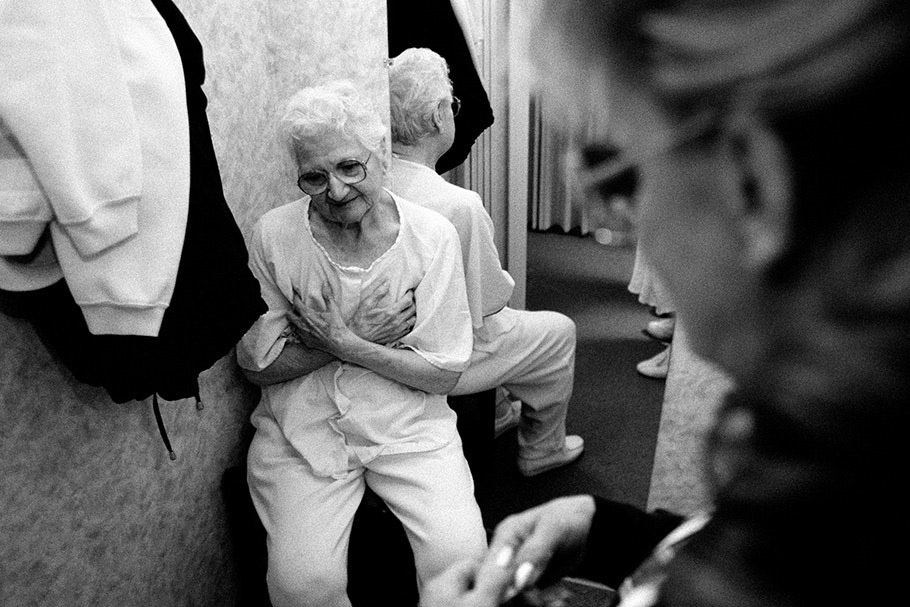 An elderly woman holds her hands to her chest.