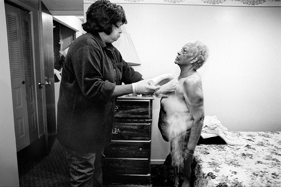 A caregiver powdering an elderly woman.