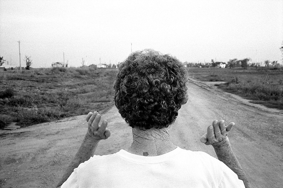 A woman, viewed from behind, surveys a landscape.