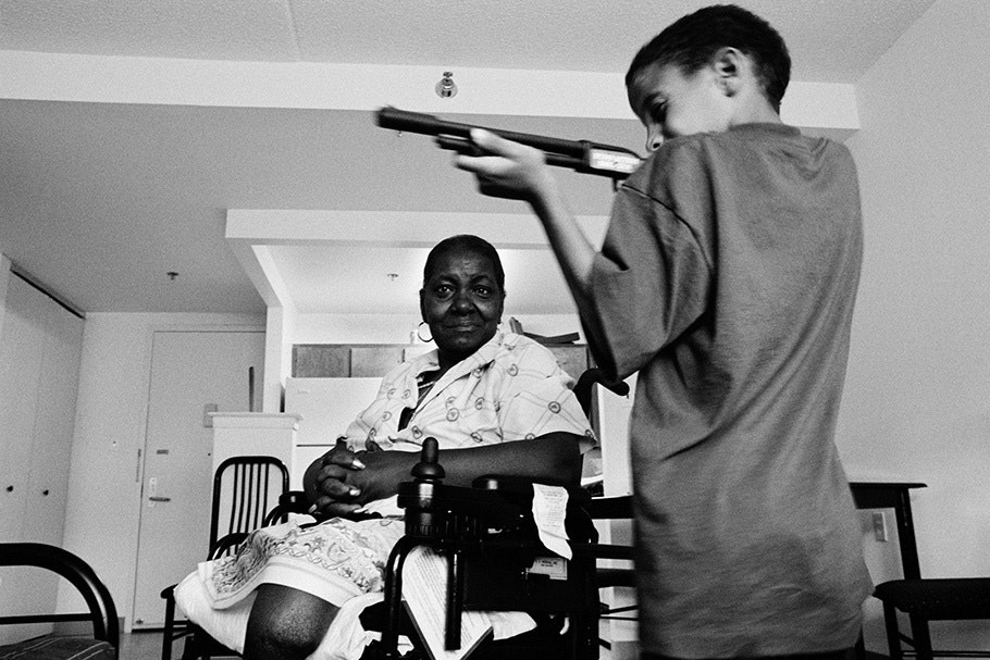 A woman watches her grandson play with a toy gun.