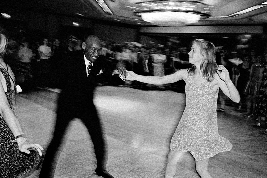 An elderly man dances with a young woman.
