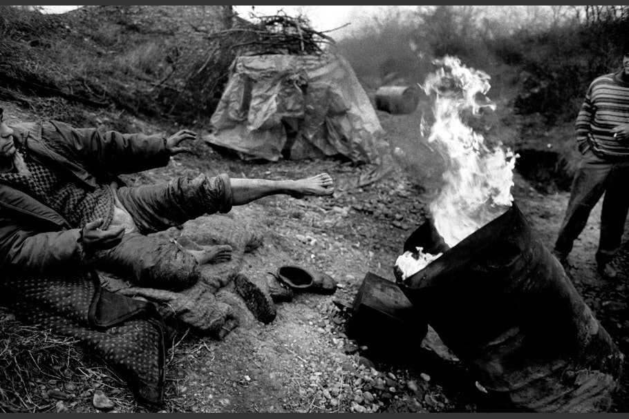 A man warms his feet by a fire in a barrel.