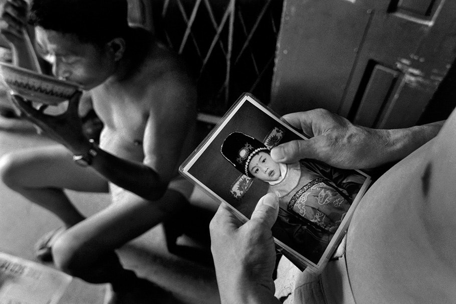 A man looks at a photograph of his son.