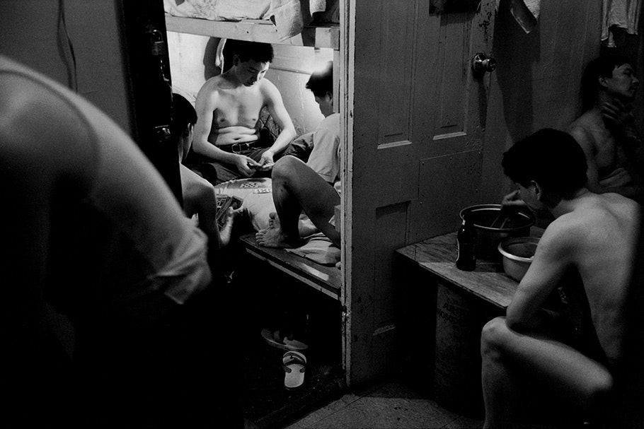 Men playing cards in a small space.