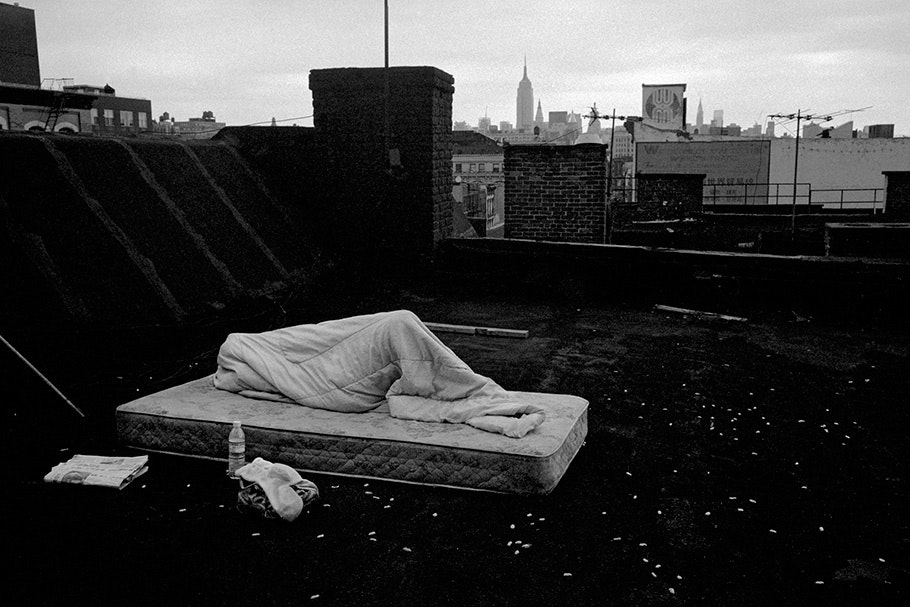 A person sleeping on a mattress on a roof.