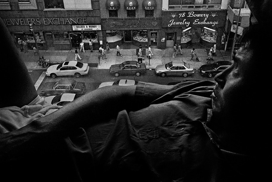 A man in a window overlooking the Bowery.