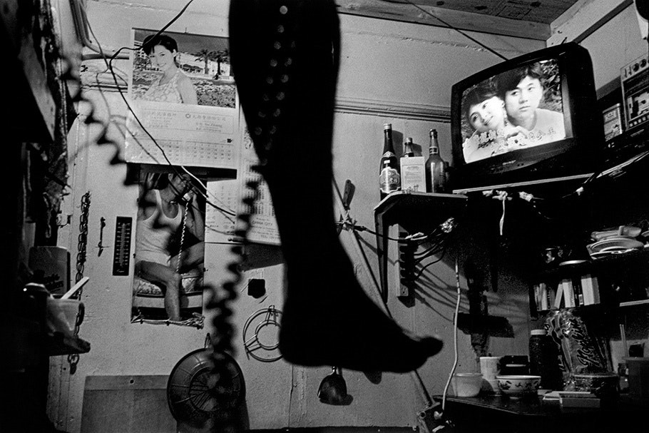 A foot dangling with a TV in the background.