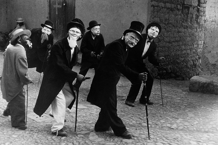 Men in masks and suits dancing.