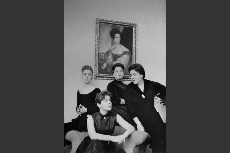 Women posing in front of a painting.