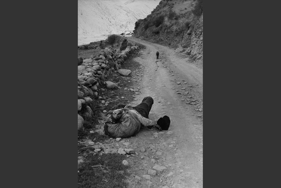 A man lying on a road.