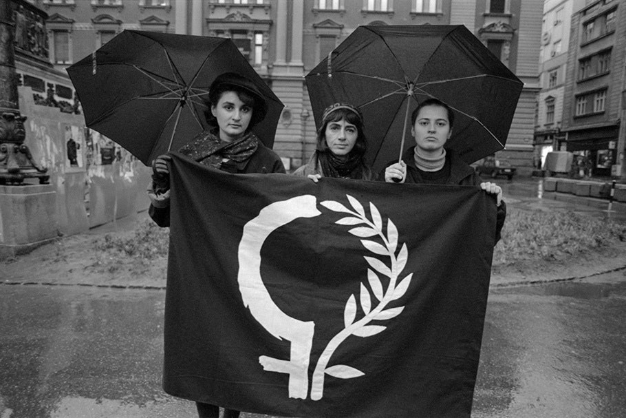 Three women holding a banner and umbrellas.
