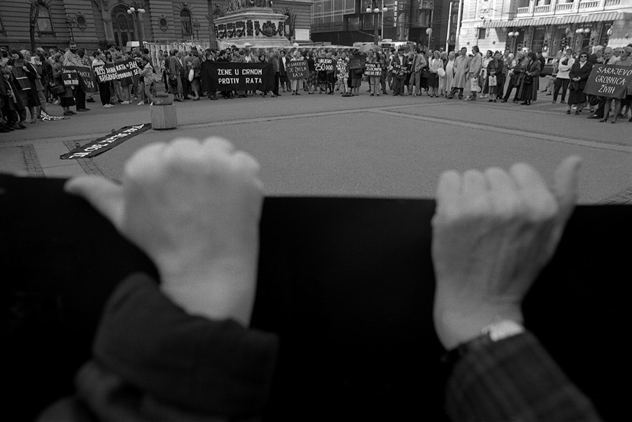 Hands holding a banner at a protest.