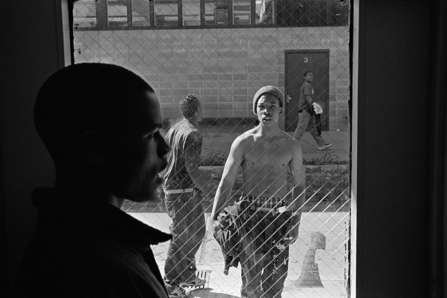 A teenage boy's profile with two more viewed through a window.