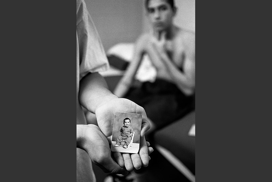 A hand holding a photo of an infant.