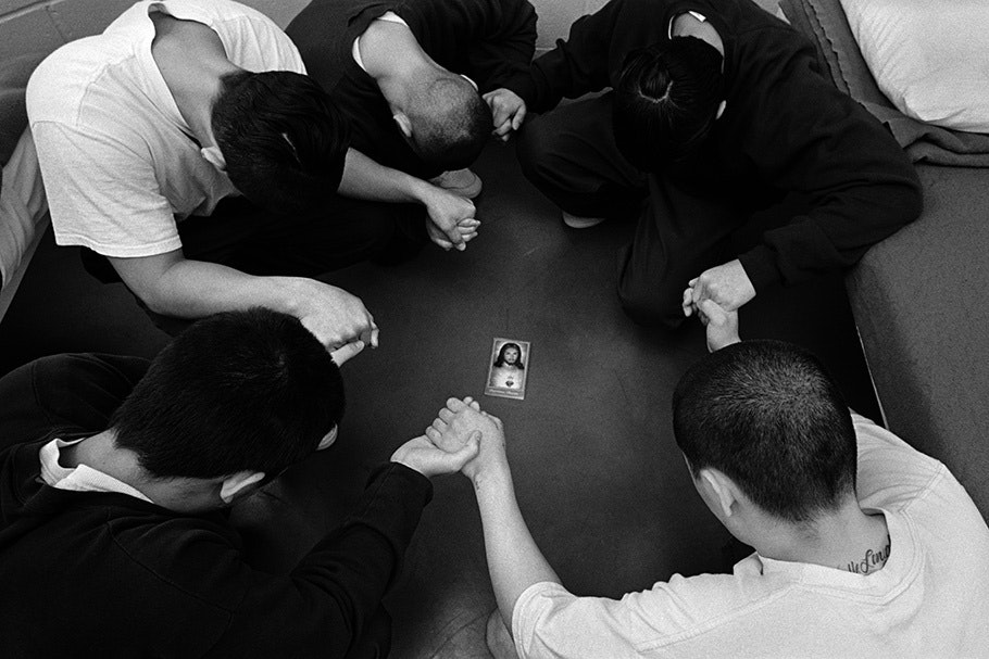 A group praying around an image of Jesus.