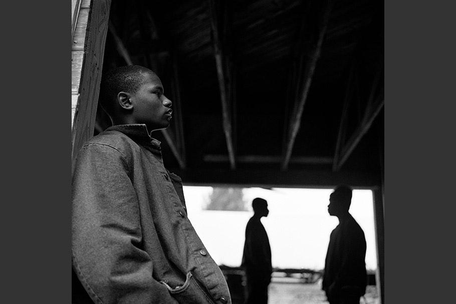 Three teenage boys seen in profile.