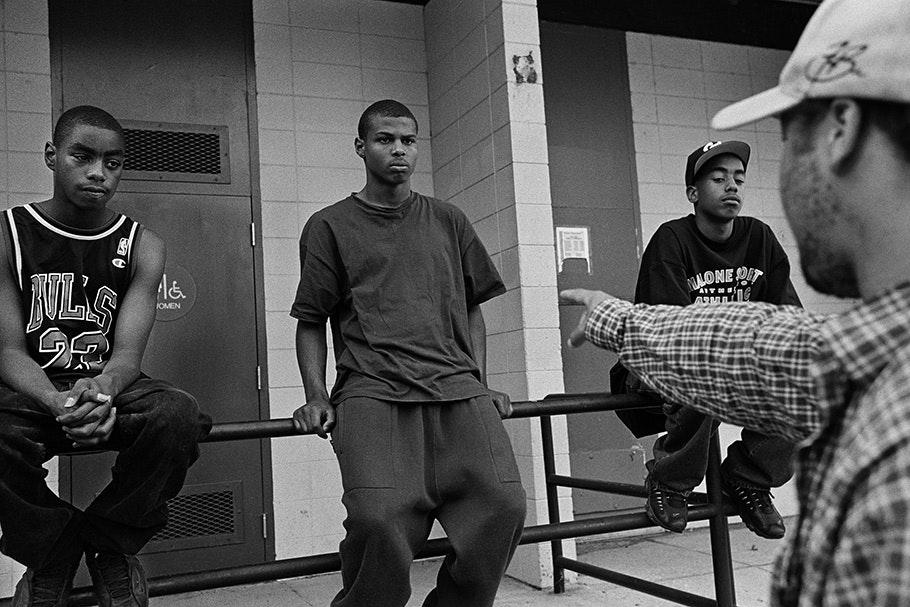 A man points at three teenage boys.